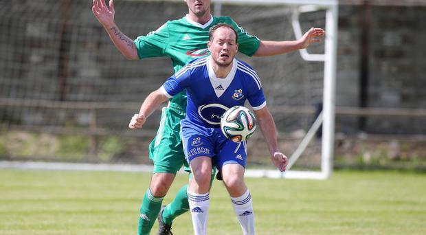Pain game: Loughgall's James Costello takes a hit from behind