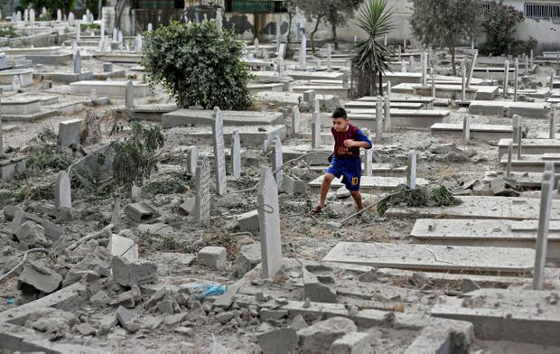A Palestinian boy runs on rubble of damaged graves at a cemetery hit by an Israeli strike in Gaza City, Sunday, Aug. 10, 2014. (AP Photo/Lefteris Pitarakis)