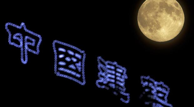 The super moon rises over a Chinese words reads