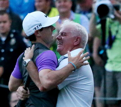 Rory McIlroy celebrates victory on the 18th green with his father Gerry McIlroy (Photo by Andrew Redington/Getty Images)