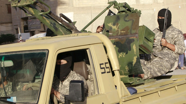 Isis fighters take part in a military parade in Syria