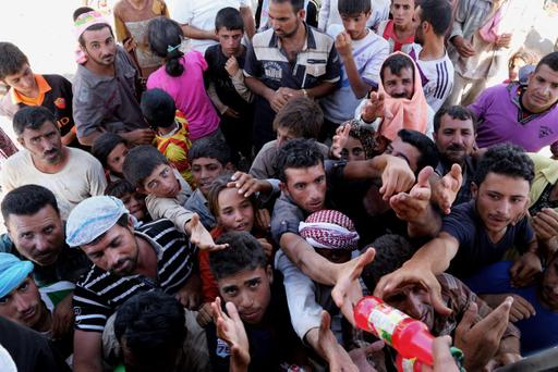 Displaced Iraqis from the Yazidi community gather for humanitarian aid at the Iraq-Syria border at Feeshkhabour border point (AP Photo/Khalid Mohammed)