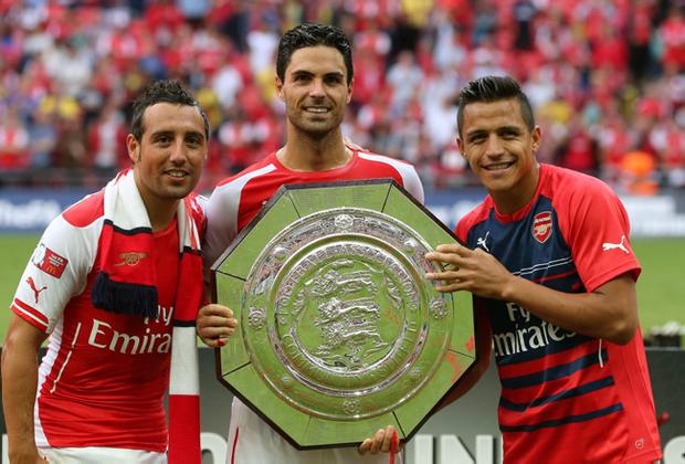 LONDON, ENGLAND - AUGUST 10: Mikel Arteta of Arsenal holds up the trophy next to Santi Cazorla (L) and Alexis Sanchez after the FA Community Shield match between Manchester City and Arsenal at Wembley Stadium on August 10, 2014 in London, England. (Photo by David Rogers/Getty Images)
