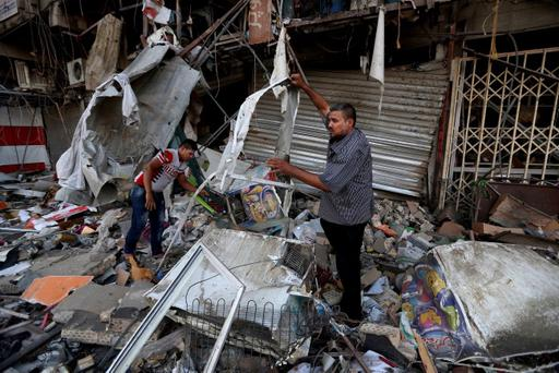 Civilians salvage what they can of their belongings at the site of a car bomb attack in central Baghdad's busy commercial Karradah neighborhood, Iraq, Wednesday, Aug 13, 2014.(AP Photo/Hadi Mizban)