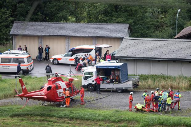 Rescue forces recover a victim of today's train crash, right, near Tiefencastel, Switzerland, Wednesday, Aug.13, 2014 (AP Photo/Keystone, Arno Balzarini)