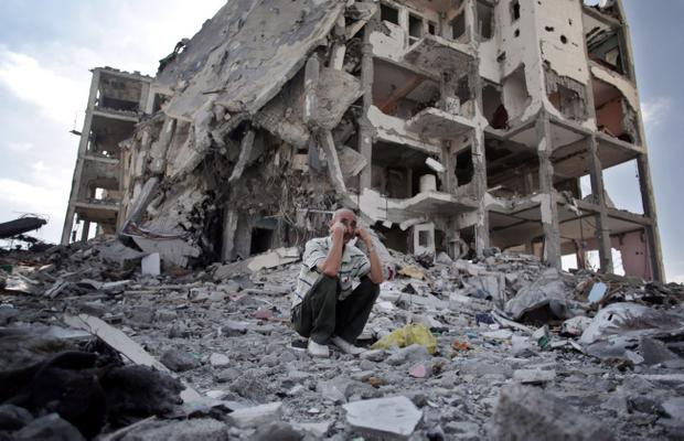 A Palestinian man rests in front of the destroyed Nada Towers in the town of Beit Lahiya, northern Gaza Strip, Monday, Aug. 11, 2014. (AP Photo/Khalil Hamra)
