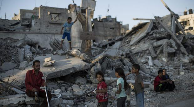 Families gather outside an area of destroyed buildings on August 14, 2014 in Shu Jaia, Gaza. (Photo by Dan Kitwood/Getty Images)