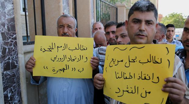 Displaced Christians and Yazids gather outside diocese of Zakho, 300 miles (475 kilometers) northwest of Baghdad, Iraq, Saturday, Aug. 16, 2014, during the visit of Cardinal Fernando Filoni, the Pope Francis special envoy to Iraq. The Arabic on the banners reads