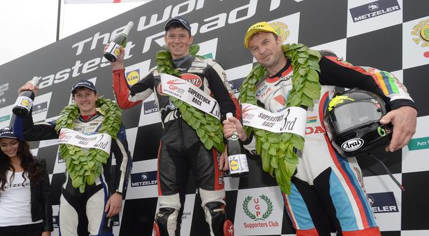 Home first: Dan Kneen celebrates winning the Superstock race with runner-up Dean Harrison and third placed Bruce Anstey