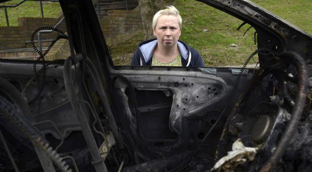 Leanne Marshall looks at the damage caused to her own car after it was burned out on the Limestone Road in north Belfast. Pic Colm Lenaghan/Pacemaker