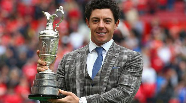 Golfer Rory McIlroy of Northern Ireland poses with the Claret Jug at half-time during the Barclays Premier League match between Manchester United and Swansea City at Old Trafford on August 16, 2014 in Manchester, England. (Photo by Alex Livesey/Getty Images)