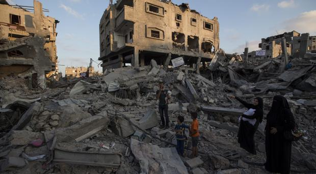 A Palestinian family walks through the rubble of a destroyed area of housing on August 16, 2014