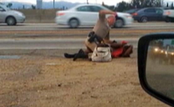 A California Highway Patrol officer punches Marlene Pinnock, 51, on the shoulder of a Los Angeles freeway (Credit: David Diaz)