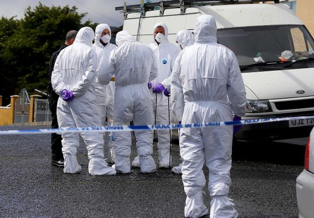 Forensic officers at the scene of a shooting in north Belfast, which police have blamed on feuding loyalists. Photo Kevin Scott