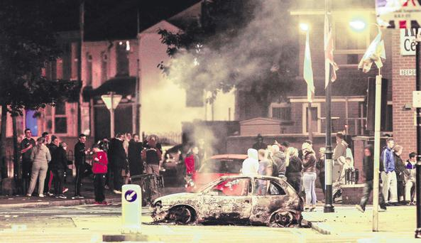 Onlookers mill around the streets of east Belfast after a car was burnt out on Tuesday night
