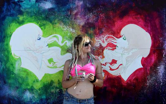 A woman poses in front of a paining during Burning Man in the Black Rock Desert of Gerlach, Nev. Organizers call Burning Man the largest outdoor arts festival in North America, with its drum circles, decorated art cars, guerrilla theatrics and colorful theme camps. (AP Photo/The Reno Gazette-Journal, Andy Barron)