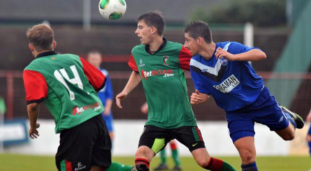 © TONY HENDRON/Presseye.com. The Park. Steele and Sons Cup Round 2. Glentoran 2nds v Ballymoney United. Glens' Stephen Boyd, left, and Mason McSorley and Ballymoney's Lee McLelland