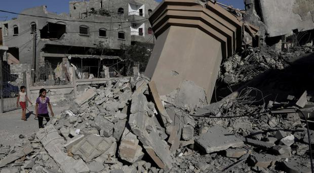 Palestinian girls inspect the rubble of Omar Ibn Abed Al-Aziz mosque, which was hit by an Israeli strikes in Beit Hanoun, in the northern Gaza Strip (AP Photo/Adel Hana)
