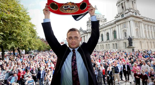 Frampton raises his IBF title belt to the roars of a massive crowd at Belfast City Hall yesterday