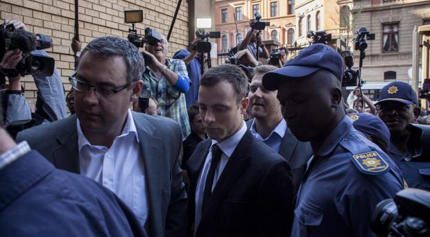 Oscar Pistorius (C) arrives at the High Court on September 11, 2014 in Pretoria, South Africa. South African Judge Thokosile Masipa is due to give her verdict as the six month trial of Olympic double-amputee sprinter Oscar Pistorius comes to an end today.