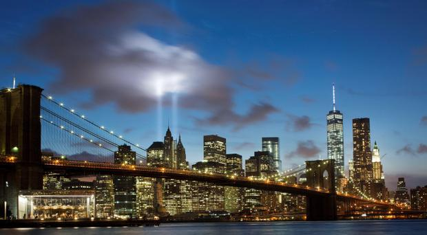 The Tribute in Light rises behind the Brooklyn Bridge and buildings adjacent to the World Trade Center complex, Wednesday, Sept. 10, 2014 (AP Photo/Mark Lennihan)