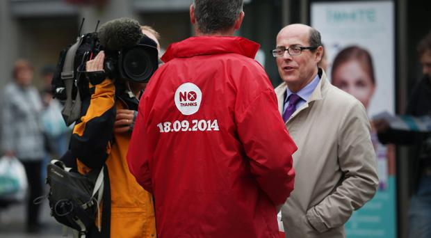 BBC TV political editor Nick Robinson (R) interviews a No campaigner near Union Street on September 15, 2014 in Aberdeen,Scotland