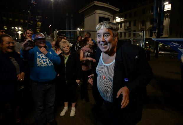 A supporter dressed as Scottish cult TV character Rab C Nesbett plays to the crowd at a