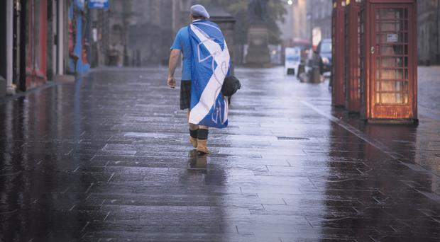 A man wrapped in a Scottish flag