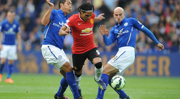 Leicester City's Leonardo Ulloa (left) and Leicester City's Esteban Cambiasso (right) challenge Manchester United's Radamel Falcao (centre) fo the ball during the Barclays Premier League match at the King Power Stadium, Leicester. Nigel French/PA Wire.