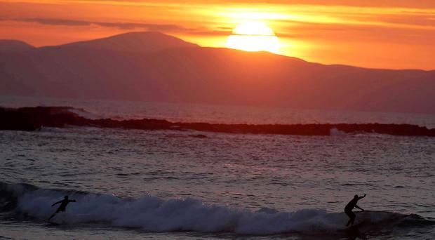 A surfer on Portrush Strand as the sun goes down over the north coast in Co Antrim
