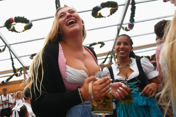 MUNICH, GERMANY - SEPTEMBER 20: A reveller dressed in traditional Bavarian clothing `Dirndl` holds a beer mug at Schottenhamel beer tent during the opening day of the 2014 Oktoberfest at Theresienwiese on September 20, 2014 in Munich, Germany. The 181st Oktoberfest will be open to the public from September 20 through October 5 and traditionally draws millions of visitors from across the globe in the world's largest beer fest. (Photo by Alexander Hassenstein/Getty Images)