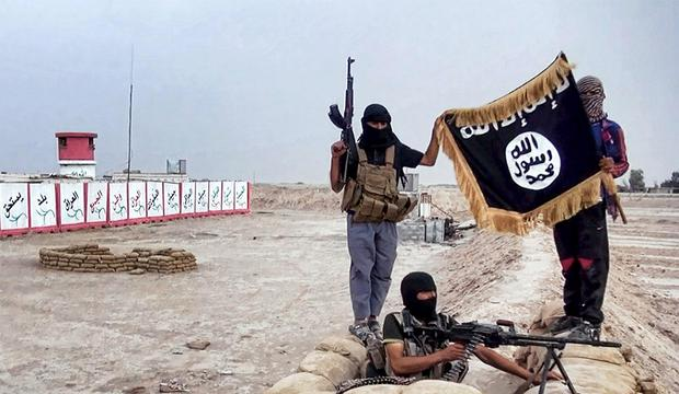 Islamic State (Isis) rebels show their flag after seizing an army post