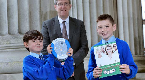 Education Minister John O'Dowd with Eoin Millar from St Colman's Primary School, Lambeg, and (right) Eoghan McConville
