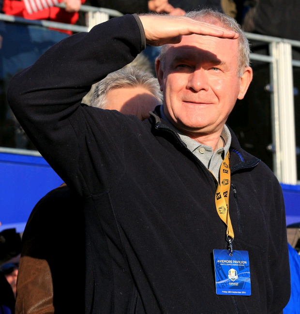 Martin McGuinness watches the Morning Fourballs of the 2014 Ryder Cup at Gleneagles, with the familiar hairline of Peter Robinson lurking behind him.