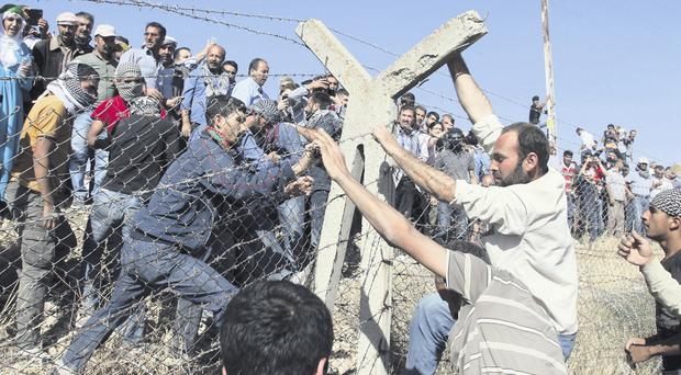 Kurds from Turkey (left) and Syria break down barbed wire at the Turkey-Syria border after a call for mass mobilisation against IS by the imprisoned leader of the PKK rebel group, Abdullah Ocalan