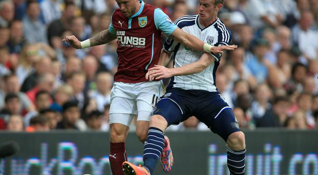 Burnley's Michael Kightly (left) battles for the ball with West Bromwich Albion's Chris Brunt during the Barclays Premier League match at The Hawthorns, West Bromwich. Nick Potts/PA Wire.