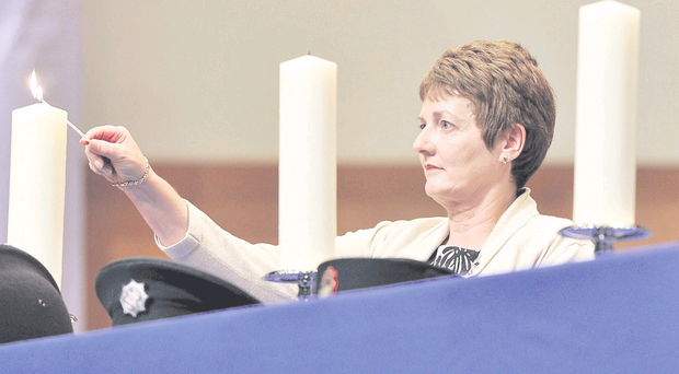 Janice Taylor of the RUC George Cross Widows Association lights a memorial candle at yesterday's ceremony in the Waterfront Hall in Belfast