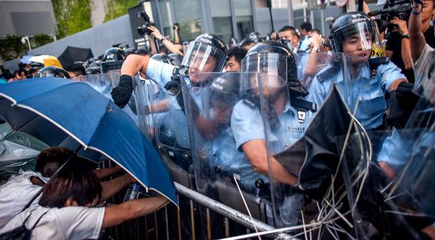 HONG KONG - SEPTEMBER 27: Police officers reacts outside Hong Kong government complex on September 27, 2014 in Hong Kong. Thousands of students from more than 20 tertiary institutions started a week-long boycott of classes in protest against Beijing's conservative framework for political reform in Hong Kong. (Photo by Anthony Kwan/Getty Images)