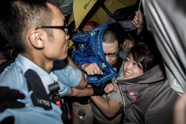 HONG KONG - SEPTEMBER 27: Protesters clash with riot police outside Hong Kong government complex on September 27, 2014 in Hong Kong. Thousands of students from more than 20 tertiary institutions start the week-long boycott of classes to protest against Beijing's conservative framwork for political reform in Hong Kong. (Photo by Lam Yik Fei/Getty Images)