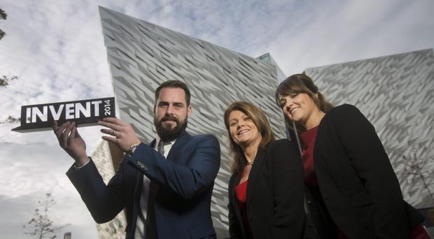 Sean and Leona McAllister of Plotbox, lift the INVENT 2014 trophy at Titanic Belfast. They are congratulated by Julie-Ann O'Hare (centre) of the awards sponsors, Bank of Ireland UK