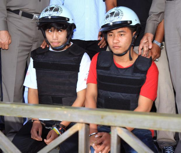 Workers from Myanmar, Saw, left, and Win, sit together, escorted by a Thai police officer, during a press conference in Koh Tao island, Surat Thani province. Thailand, Friday, Oct. 3, 2014. Thai police have arrested the two Myanmar workers they say confessed to killing a pair of British tourists on a beach in the southern Thailand last month. (AP Photo) THAILAND OUT