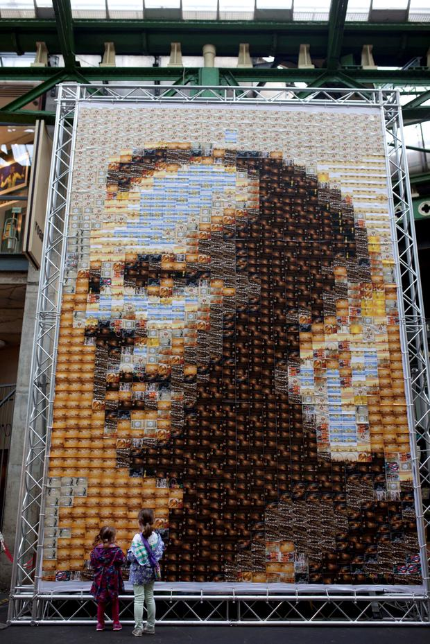 Passers-by look at the 24-metre square canvas - made from 1,485 postcards - of actor Kiefer Sutherland in character as Jack Bauer from television drama 24, which was designed by Tyrone artist Quentin Devine