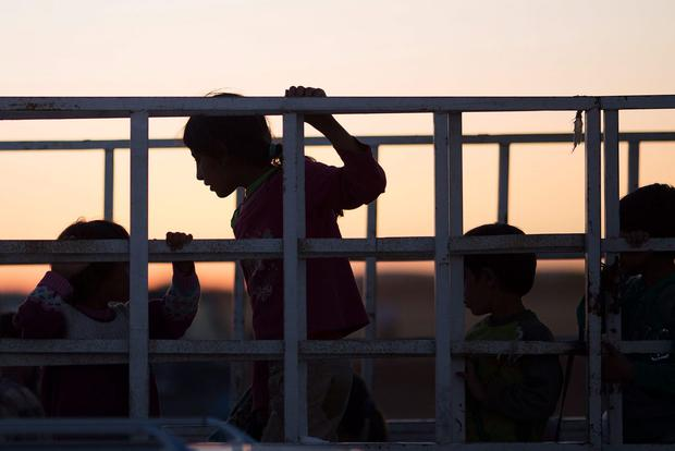 Refugees ride in the back of a truck after crossing the border from Syria into Turkey on October 1 , 2014. (Photo by Carsten Koall/Getty Images)