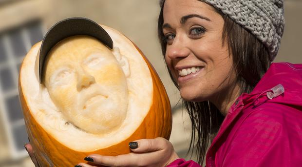 Heather Doran at the Castle Ward Pumkinfest at the weekend and photographed with a carving of a pumpkin to look like Rory McIlorys head sculptured by Joey Burnes a master pumpkin carver from Co. Carlow.