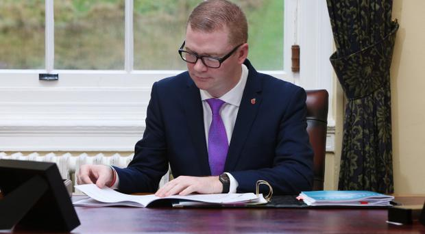 Finance Minister Simon Hamilton pictured with the Executive's draft budget