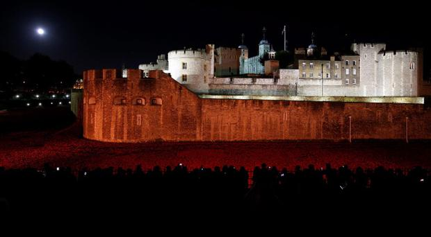 Members of the public stop to look at the ceramic poppies which form part of the art installation 'Blood Swept Lands and Seas of Red' by artist Paul Cummins at the Tower of London. Pic Jonathan Brady/PA Wire