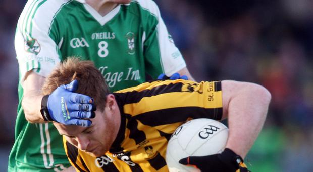 Up close: Eamon Doherty of St Eunan's proves a handful for Roslea captain James Sherry yesterday