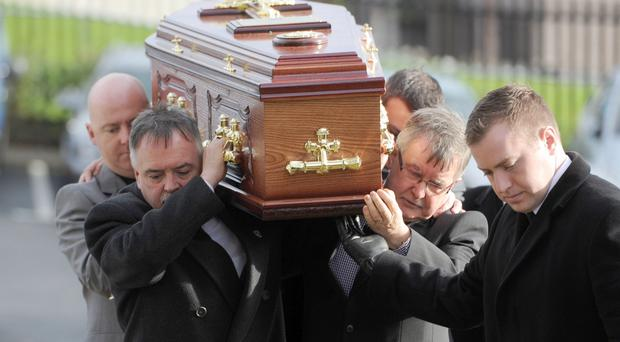 Kieran Megraw (left) and his brother Sean carry their brother Brendans coffin into the church. Pic Declan Roughan.