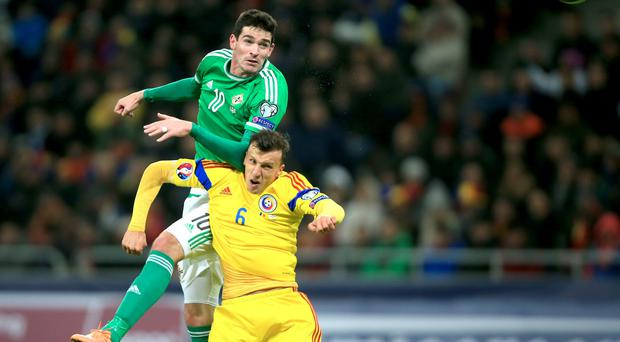 Leading the line: Kyle Lafferty rises for a header during last night's Euro 2016 qualifier in Bucharest