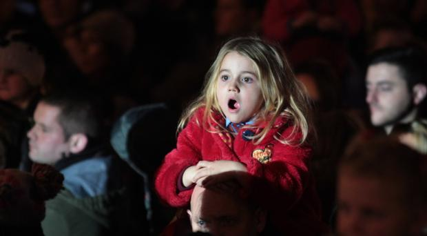 A young spectator at Londonderry's Christmas lights switch-on spots a familiar white-bearded man on the city's walls during last night's ceremony, which was attended by a crowd of around 10,000 people
